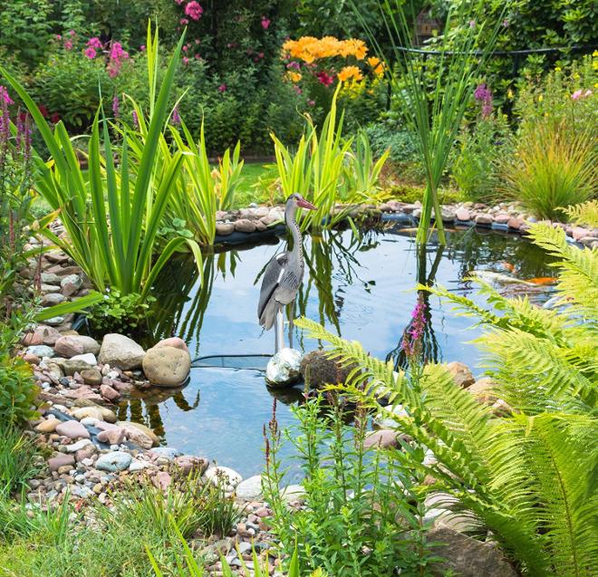 Reiherfigur steht im Teich
